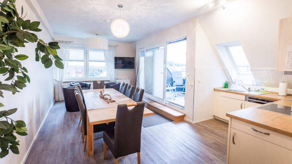 Unterkunft Gruppenunterkunft Monteurzimmer in Meckelfeld. Loggia, Esszimmer mit großem Tisch und Stühlen und Küche.